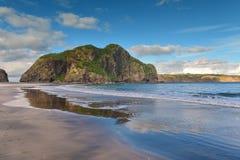 Los acantilados y las formaciones de roca a lo largo de la arena negra Whatipu varan en Huia Imagen de archivo libre de regalías