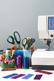Los accesorios de costura en una cesta y los carretes de hilos al lado de cosen Imagenes de archivo