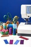 Los accesorios de costura en una cesta y los carretes de hilos al lado de cosen Imágenes de archivo libres de regalías