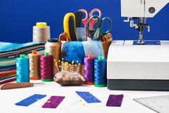 Los accesorios de costura en una cesta y los carretes de hilos al lado de cosen Foto de archivo