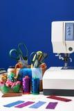 Los accesorios de costura en una cesta y los carretes de hilos al lado de cosen Imagen de archivo
