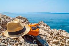 Los accesorios de la playa del verano se fueron en una playa rocosa con un swi de la persona Fotos de archivo