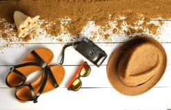 Los accesorios de la playa se presentan en una superficie de madera blanca Sombrero, cámara, sandalias, gafas de sol El concepto  Imágenes de archivo libres de regalías