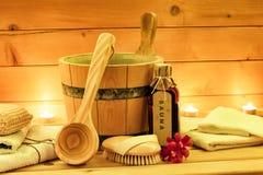 Los accesorios de la sauna con sauna engrasan, cubo de madera, cucharón, toallas Foto de archivo