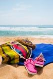 Los accesorios de las mujeres en la playa arenosa Fotografía de archivo libre de regalías