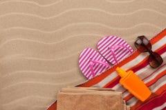 Los accesorios de las mujeres para la playa que miente en la arena Imagen de archivo