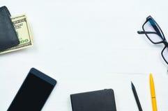 Los accesorios de los hombres clásicos: cartera, dólares, teléfono, cuaderno, pluma, vidrios Imagenes de archivo