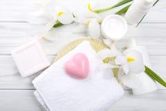 Los accesorios del baño con las flores hermosas en la tabla de madera, top compiten Foto de archivo libre de regalías