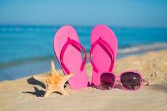 Los accesorios del mar, de la playa, de la arena y de las mujeres: balanceos rosados, gafas de sol y estrellas de mar Imagenes de archivo