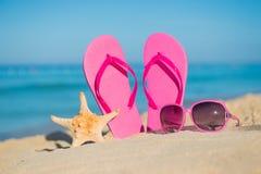 Los accesorios del mar, de la playa, de la arena y de las mujeres: balanceos rosados, gafas de sol y estrellas de mar Fotografía de archivo