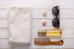 Los accesorios del mar en fondo de madera broncean el aceite, peine, toalla, conchas marinas, gafas de sol imagen de archivo