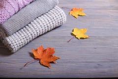 Los accesorios del otoño hicieron punto los suéteres y las hojas Foto de archivo