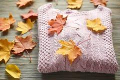 Los accesorios del otoño hicieron punto los suéteres y las hojas Foto de archivo libre de regalías
