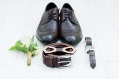 Los accesorios del ` s de los hombres del novio en la boda se exponen por una aún-vida en una lamina de la luz Zapatos del ` s de Imagen de archivo