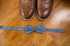 Los accesorios del ` s del novio Corbata de lazo azul y una pieza de zapatos de cuero marrones en un fondo de madera Imagen de archivo libre de regalías