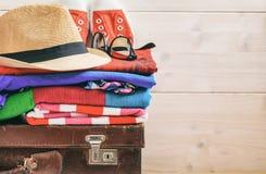 Los accesorios del viaje en una maleta y un fondo blanco - copie el espacio Foto de archivo
