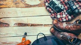 Los accesorios del viaje fijaron en fondo de madera con el espacio: viejos botas de cuero, mochila, cámara y viaje L de la pelícu Fotografía de archivo libre de regalías