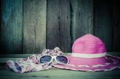Los accesorios del viaje para el sombrero de las mujeres jovenes pican las gafas de sol de la bufanda En la madera Foto de archivo