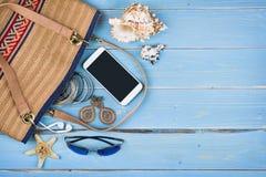 Los accesorios femeninos del viaje sobre azul tropical texturizaron el fondo de madera Imagen de archivo libre de regalías