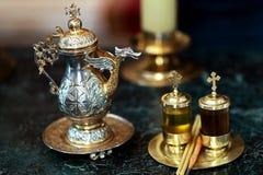 Los accesorios para el bautismo del niño según las tradiciones de la iglesia son platos dorados en una tabla oscura Fotografía de archivo