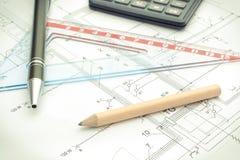Los accesorios y la calculadora del dibujo en la vivienda planean, el concepto casero del coste del edificio Foto de archivo