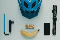 Los accesorios y la comida de ciclo se prepararon para un paseo de la bici, en fondo azul Imagen de archivo libre de regalías