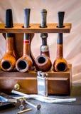 Los accesorios y los tubos de tabaco en una madera instalan tubos para los fumadores Fotografía de archivo