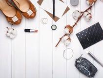 Los accesorios, los zapatos y el algodón femeninos ramifican en la tabla blanca Imagenes de archivo