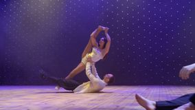 Los acróbatas hermosos realizan trucos de la elegancia en la etapa en teatro almacen de video