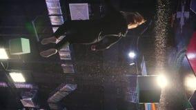 Los acróbatas juguetones jovenes de la mujer realizan trucos acrobáticos - saltando en un pasillo del trampolín, cámara lenta - l metrajes