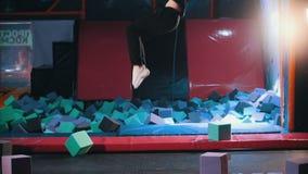 Los acróbatas juguetones jovenes de la mujer realizan trucos acrobáticos - saltando en un pasillo del trampolín, a cámara lenta almacen de metraje de vídeo