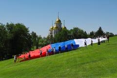 Los activistas despliegan una bandera grande de Rusia el día de Rusia en Mamaev Kurgan en Volgog Fotografía de archivo