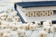 Los activos redactan escrito en el bloque de madera Fotos de archivo