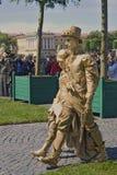 Los actores de la calle en trajes de oro caminan en el cuadrado de Dvortsovaya en St Petersburg Imagen de archivo libre de regalías