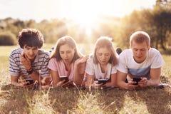 Los adolescentes adictos que son siempre adentro el tacto, mentira en hierba verde, utilizan los teléfonos móviles durante el res Imágenes de archivo libres de regalías