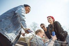 Los adolescentes agrupan divertirse con el carro de la compra en el parque del monopatín Foto de archivo libre de regalías