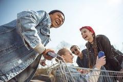 Los adolescentes agrupan divertirse con el carro de la compra en el parque del monopatín Imágenes de archivo libres de regalías