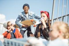 Los adolescentes agrupan divertirse junto en rampa en el parque del monopatín Imagenes de archivo