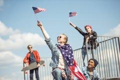 Los adolescentes agrupan divertirse junto y agitar banderas americanas Imágenes de archivo libres de regalías