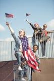 Los adolescentes agrupan divertirse junto y agitar banderas americanas Imagen de archivo