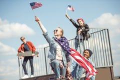 Los adolescentes agrupan divertirse junto y agitar banderas americanas Imagen de archivo libre de regalías