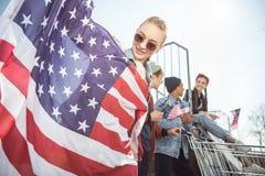 Los adolescentes agrupan divertirse y agitar banderas americanas en la puesta del sol Imagenes de archivo