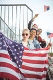 Los adolescentes agrupan divertirse y agitar banderas americanas en la puesta del sol Imagen de archivo libre de regalías