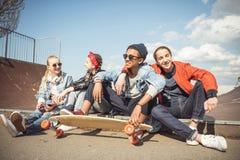 Los adolescentes agrupan sentarse juntos y hablar en el parque del monopatín Fotos de archivo libres de regalías