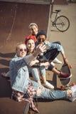 Los adolescentes agrupan tomar el selfie del inconformista mientras que se sientan juntos en el parque del monopatín Fotografía de archivo
