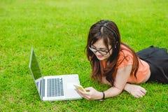 Los adolescentes asiáticos sientan uso recreativo del teléfono elegante Imagen de archivo libre de regalías
