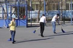 Los adolescentes barren la yarda con los barrenderos durante un trabajo d de la comunidad Fotografía de archivo libre de regalías