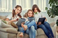 Los adolescentes con el ordenador de la PC de la tableta y la música que escucha de los auriculares y comunican en redes sociales Imagen de archivo