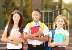 Los adolescentes con las mochilas y los cuadernos en escuela encantan el fondo Imágenes de archivo libres de regalías