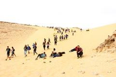 Los adolescentes consiguen de una colina de las dunas de arena imagenes de archivo